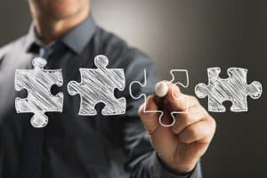 Business person drawing four jigsaw pieces