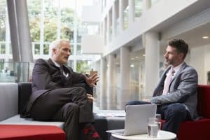 Two Businessmen Meeting In Lobby Area Of Modern Office